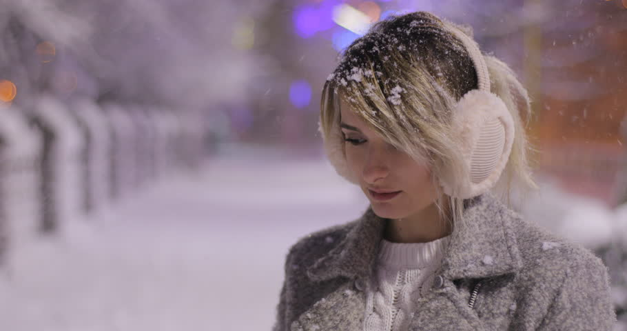 Portrait of a young smiling woman wearing ear muffs, trying to warm herself in night winter city. Winter concept. Christmas, winter holidays concept. Snowfall.