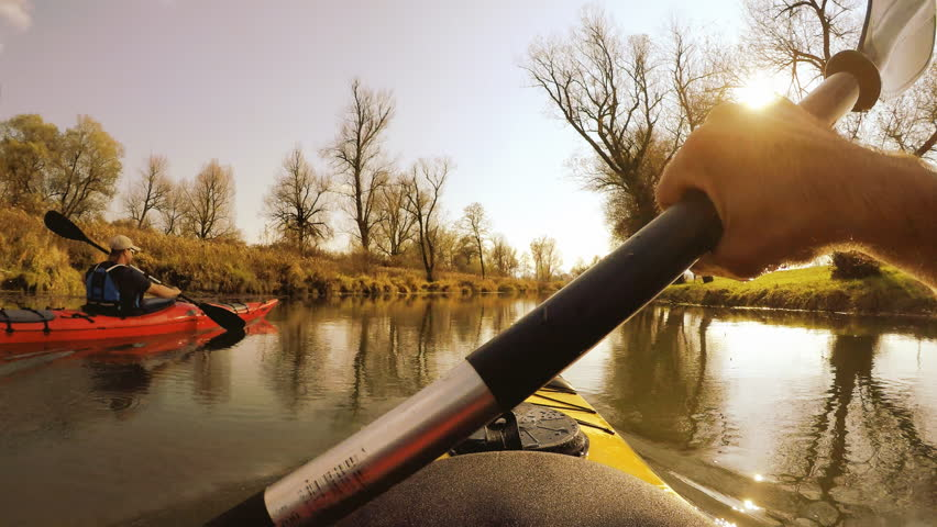 POV shot of kayakers paddling down the river in red and yellow kayak in amazing landscape on a beautiful sunny day.