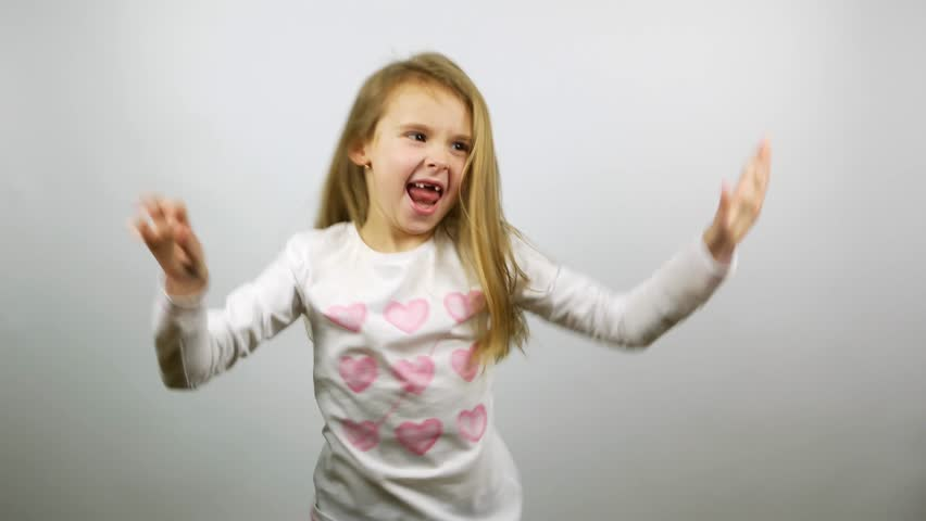 Funny child dancing. Young amusing girl rejoicing victory