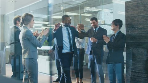 Black Businessman Got Big Promotion, Walking Path of Success, His Colleagues Cheer and Applaud. Stylish Diverse Office Filled with Happy People. Shot on RED EPIC-W 8K Helium Cinema Camera.