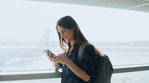 Young girl using smartphone near airport window. Happy European woman with backpack uses mobile app in terminal. 4K.