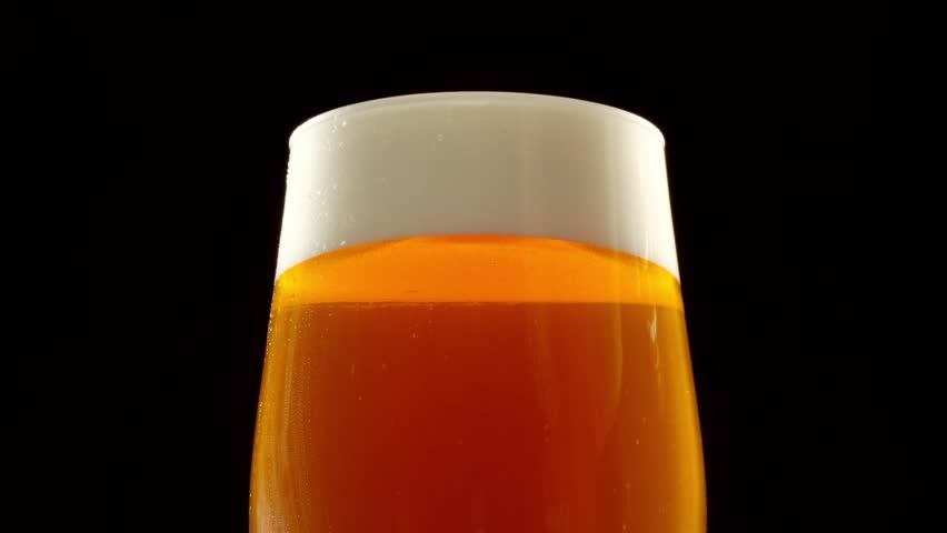 Stream of beer pours into a rotating beer glass. Close up 4K video. Black background. | Shutterstock HD Video #1008285205