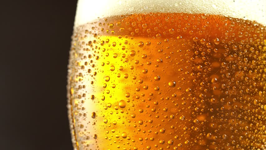 Glass of beer turns slowly around its axis. Close up 4K video. Black background. | Shutterstock HD Video #1008285265