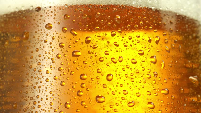 Glass of beer turns slowly around its axis. Close up 4K video. Macro shooting. | Shutterstock HD Video #1008285445