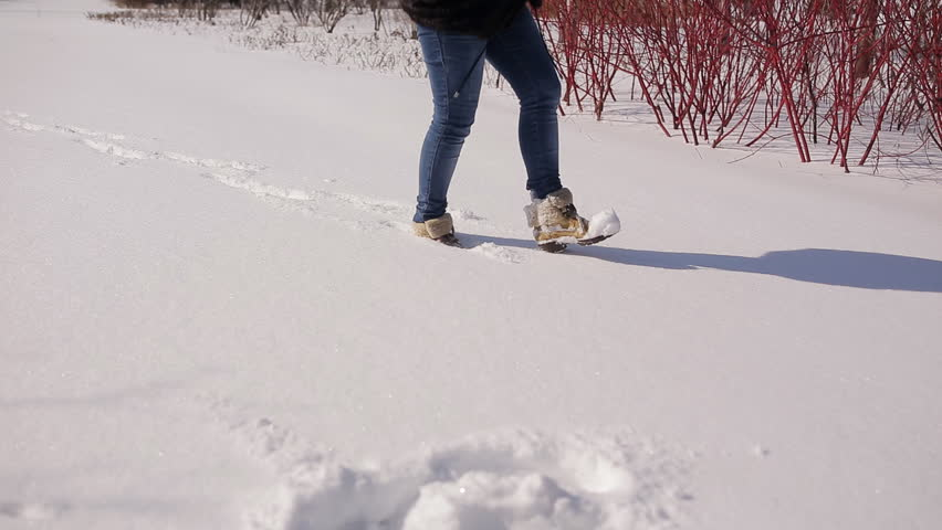 Legs of woman walking on snow with footprints on snowy day #1008290965