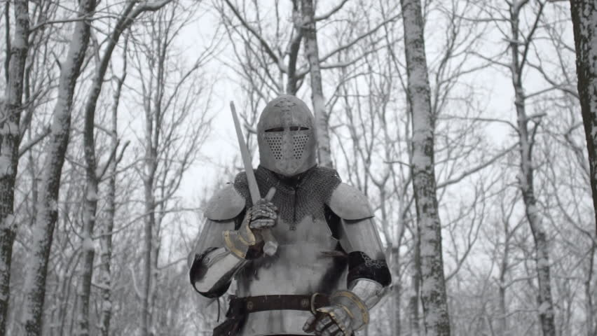 Portrait of severe medieval soldier with steel sword in hand preparing for fight in winter wood with snowy trees background, slow motion. Reconstruction of old times