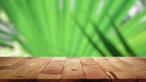 Wood table top with blurred natural green leaves being blown by gentle breeze in background