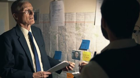 Senior Police Officer In Suit Gives Briefing Orders At Night To Uniform Cop, Map Instructions At Station. Emergency Mission 4K.