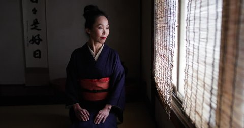 Portrait of Japanese woman wearing Kimono by traditional window looking to camera, Kyoto Japan