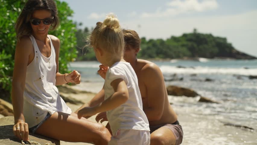 Young family enjoy time at sunny beach rapid slow motion