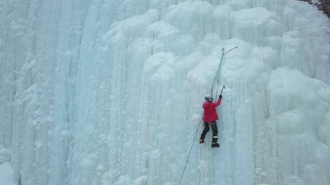 Alpinist climbs to top of huge icy wall. Aerial shot.