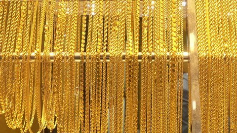4K view of lot of different gold chains in the shop window of the jewelry store.