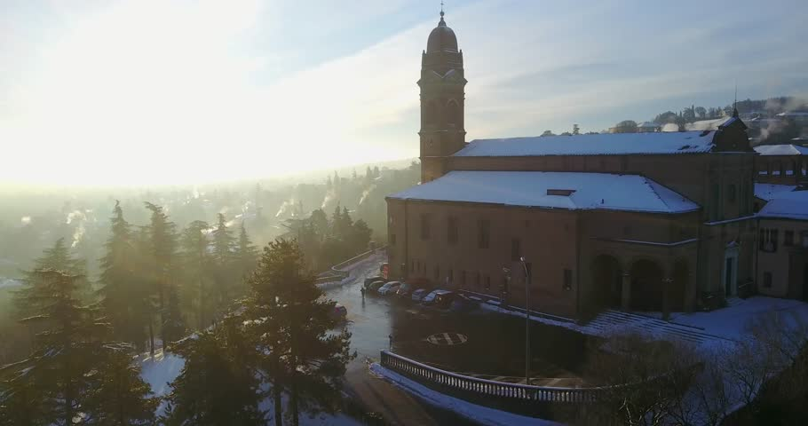 AERIAL: Cinematic view of San Michele in Bosco church covered with snow at sunshine. Bologna, Italy.