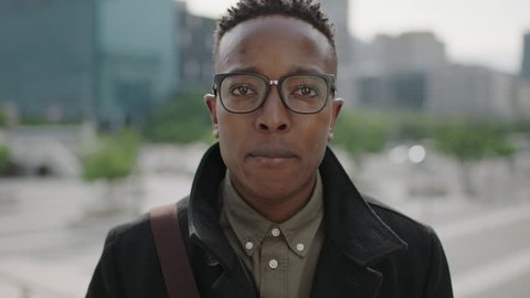 close up portrait of young happy african american man student smiling cheerful at camera wearing glasses in city successful urban lifestyle