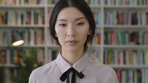 close up portrait of beautiful cute asian woman standing in library bookcase in background