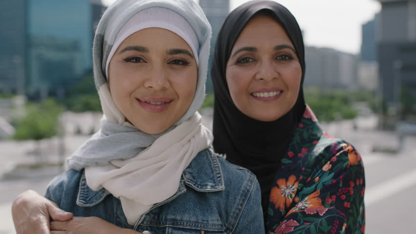 close up portrait of happy mother and daughter smiling cheerful hugging in urban city wearing traditional muslim hijab headscarf enjoying lifestyle culture family togetherness