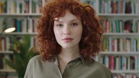 portrait of lovely young librarian woman standing in library attractive student smiling close up red head