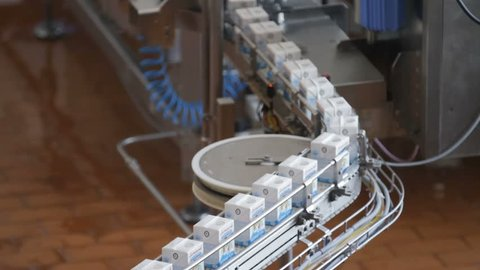 Kiev Region, Ukraine - Februry 2017: Milk package conveyor. Dairy products in tetra packaging are moving along the conveyor at a dairy factory.