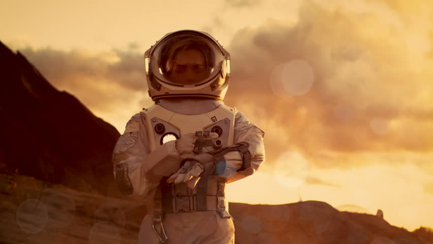 Female Astronaut Checks Data on Her Wrist Computer while Exploring Alien Red Planet/ Mars. Space Travel, Planet Colonization Concept. Shot on RED EPIC-W 8K Helium Cinema Camera. | Shutterstock HD Video #1008373375