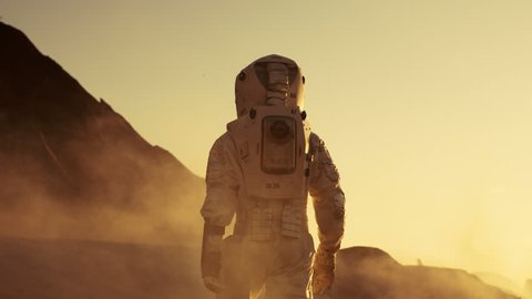 Following Shot of Astronaut Confidently Walking on Mars. Red Planet Covered in Gas and Smoke. Humans Overcoming Difficulties. Big Moment for the Human Race. Shot on RED EPIC-W 8K Helium Cinema Camera.