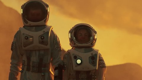 Two Astronauts Wearing Space Suits Walk Exploring Mars/ Red Planet. Space Travel, Exploration and Colonization Concept. Shot on RED EPIC-W 8K Helium Cinema Camera.
