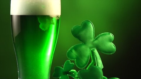 St. Patric's Day Green Beer pouring over dark green background, decorated with shamrock leaves. Patric Day pub party, celebrating. Pint of Green beer close-up. Slow motion 4K UHD video