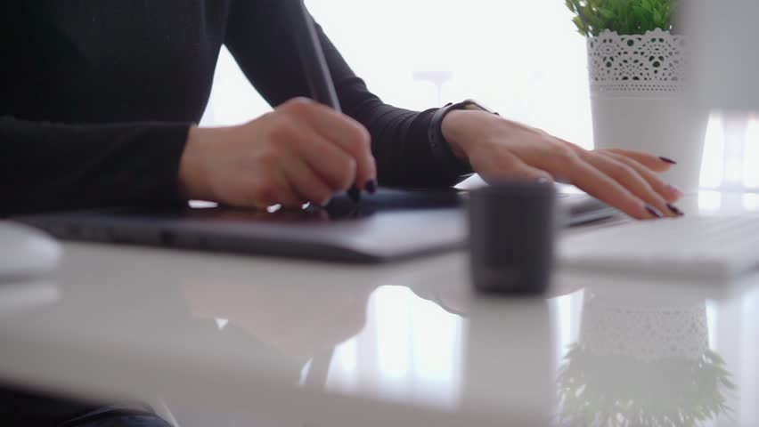 Female use a graphic tablet and stylus to work behind a modern computer screen. Young girl working distance | Shutterstock HD Video #1008394855