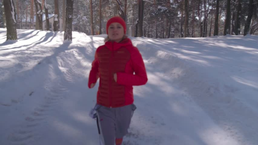 Young beauty girl in pink jacket and hat jogging to front at winter day