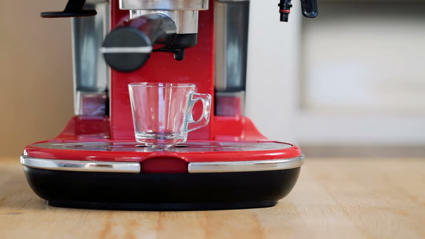 Making fresh coffee going out from a coffee espresso machine. Making espresso in glass transparent coffee cup.