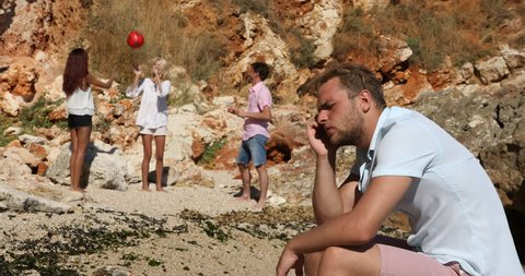 Sad Young Man Have Headache Pain Sit Far Group People Playing Beach Volleyball