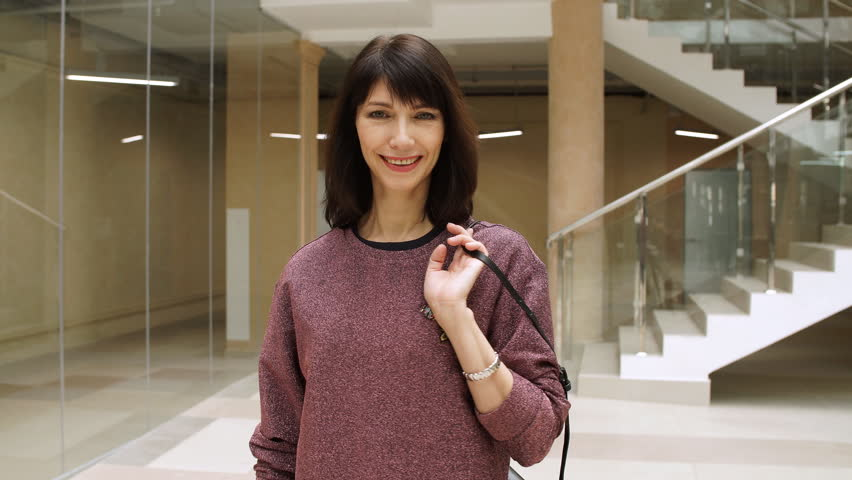 Mature woman walking confidently in mall while looking at camera. | Shutterstock HD Video #1008447385