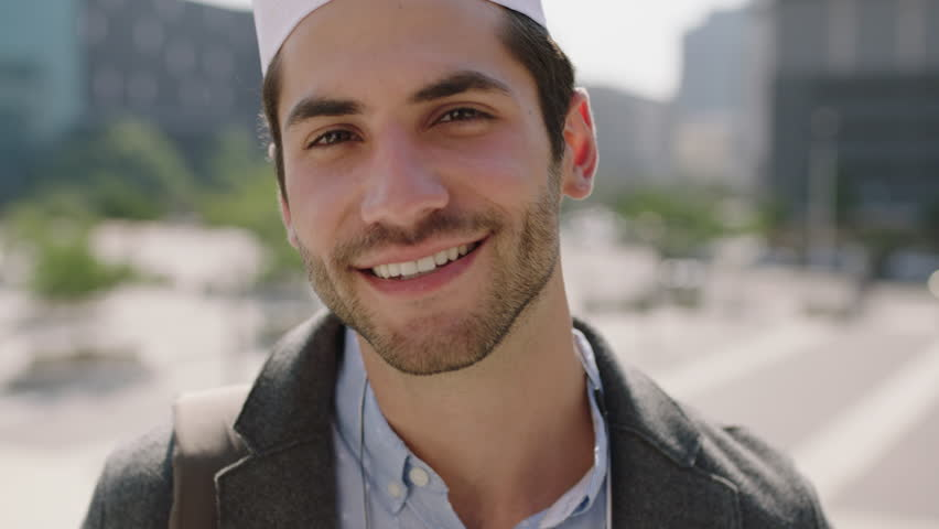 Portrait of cute young middle eastern muslim man smiling cheerful enjoying music wearing earphones in urban city background | Shutterstock HD Video #1008478165