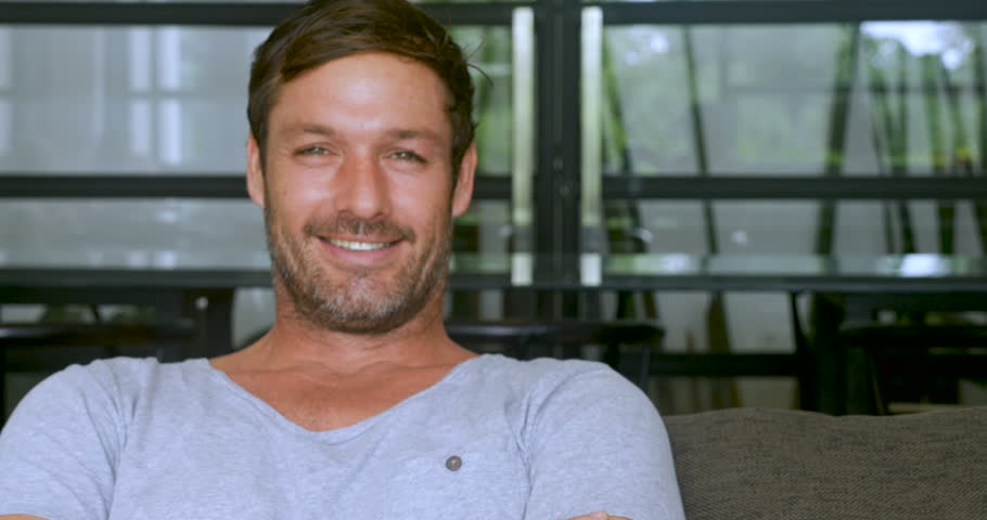 Handsome man in his 30s or 40s sitting on sofa with a scruffy beard smiling and looking at the camera