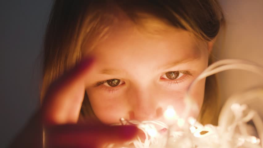 Close-up of face little girl holding a glowing garland in front of her eyes