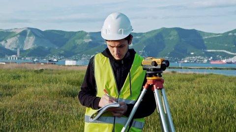 Surveyor engineer is measuring level on construction site. Geodesist ensure precise measurements before undertaking large construction projects. Concept of landscape design