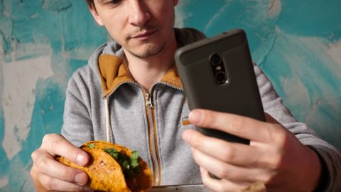 Guy takes phone selfie in Mexican cuisine restaurant during eating tacos