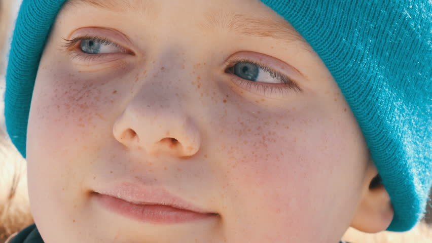 A teenager boy with an unusual color of turquoise eyes and freckles on his face in a blue hat looks aside | Shutterstock HD Video #1008538165