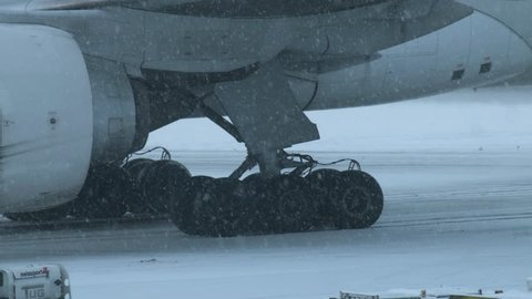 Long shot of the wheels of a commercial airplaneing down a snow covered runway during a snow storm in Montreal