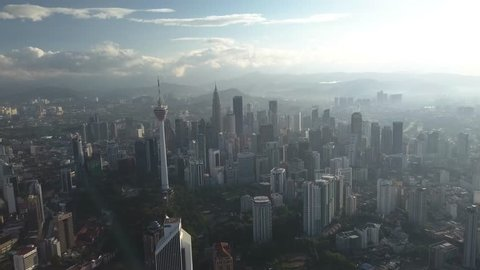 KUALA LUMPUR, MALAYSIA - MARCH 2018 : 4K aerial footages of Kuala Lumpur city buildings and landmarks including KL Tower and Petronas Twin Tower (KLCC) from a drone during sunrise.