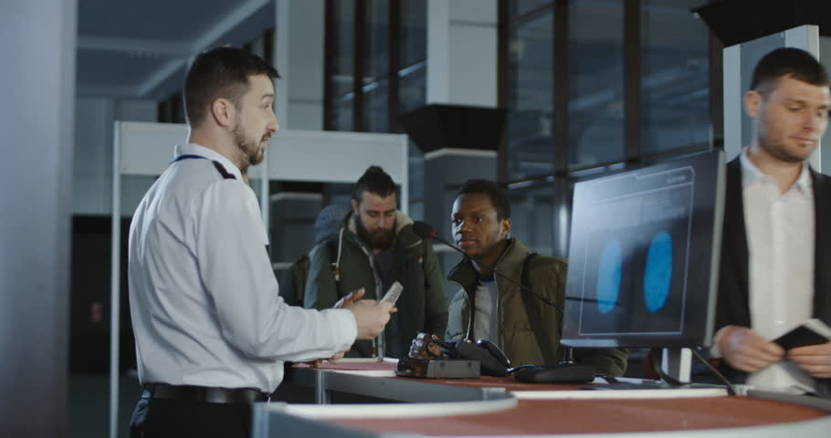 Security officer checking a male passenger thumb print and passport at an airport check-in counter with a view of the computer screen showing the scan being processed.
