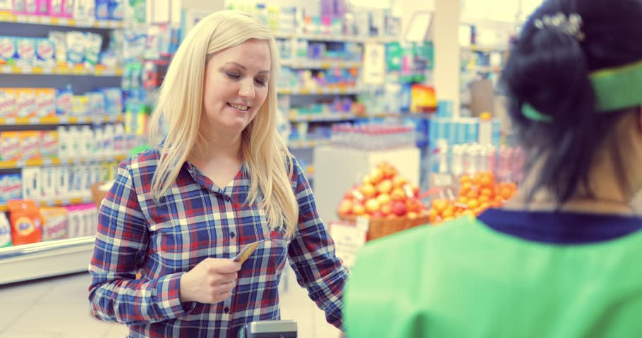 Young girl makes a purchase in a supermarket, pays at the checkout | Shutterstock HD Video #1008591355