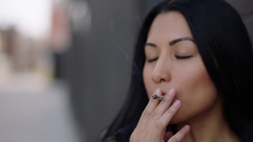 Female smoking cannabis joint outside