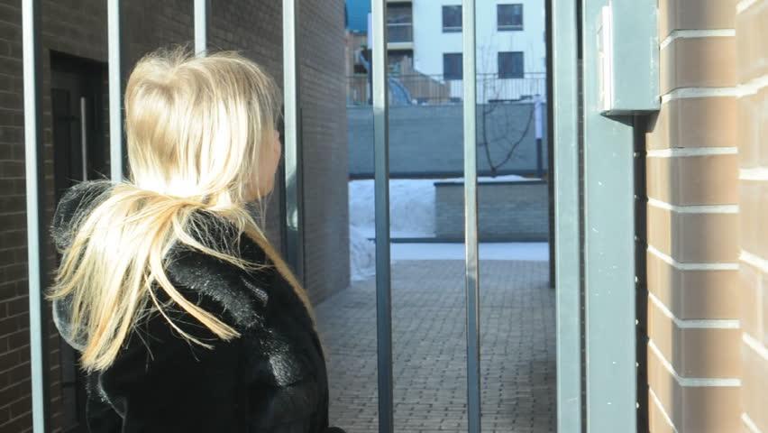 Woman dials an apartment code on an electronic doorphone panel | Shutterstock HD Video #1008614575