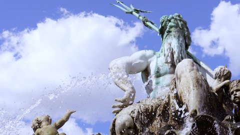 fountain with statue of Poseidon in Berlin in slowmotion and a church in the back