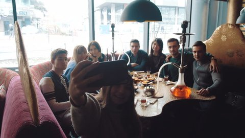 Young company is making selfie. Smoking a hookah and communicating in an oriental restaurant. Lebanon cuisine served in restaurant.