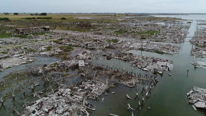 Aerial drone scene of destructed, demolished flooded Epecuén City, Buenos Aires, Argentina. From panoramic to senital view. Ends with detail of demolished houses, debris and rubble from top view.  | Shutterstock HD Video #1008623965