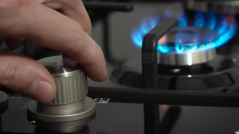 Turning on the cooktop gas cooker. Kitchen burner turning on. close up on the flame. Natural gas inflammation in stove burner, close up view.  Gas burning from a kitchen gas stove.
