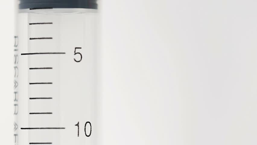 Yellow liquid flows inside plastic syringe. Nurse gets ready to inject vitamins #1008628615