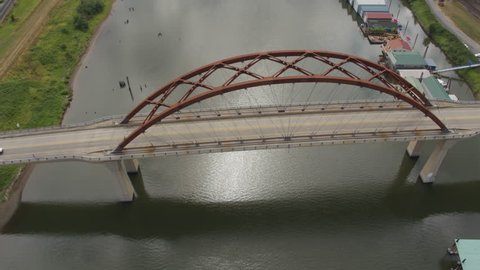 Aerial pull back-reveal of the Sauvie Island Bridge with house boats on each side