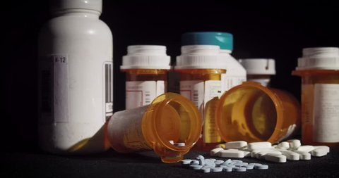 A variety of prescription medication is strewn about haphazardly.